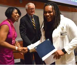 University of Wisconsin-Milwaukee senior Carl Greer receiving his graduation certificate from Dr. Doriel Ward and former MCW Trustee Chas Mulcahy