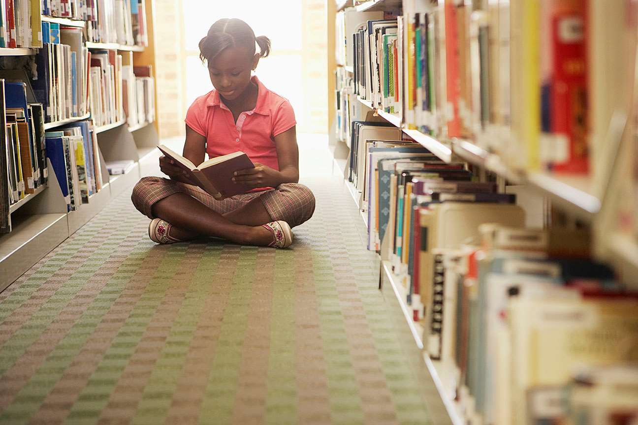 Young girl sitting reading books in library