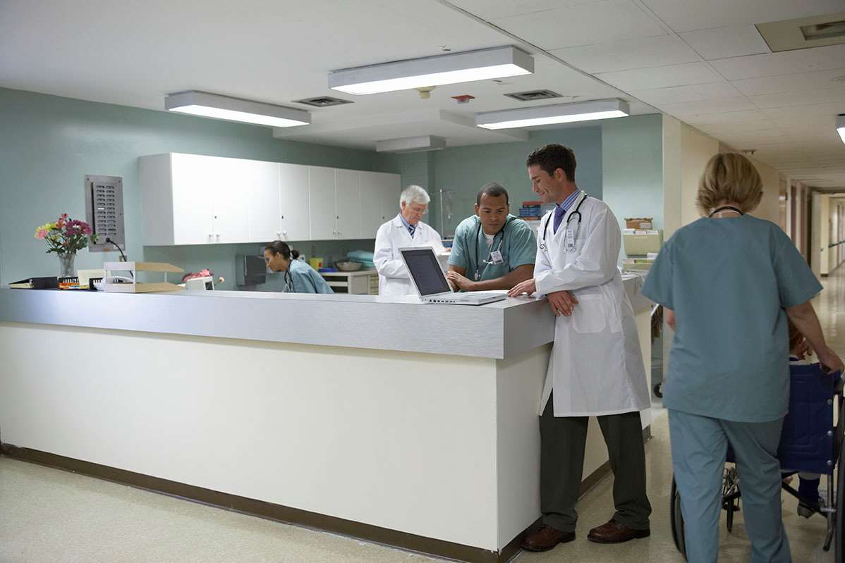 Physicians collaborate around counter in clinic